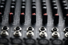 Music mixer desk. Detail of a music mixer desk with various knobs Stock Photography