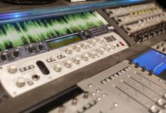 Music mixing console at sound recording studio. Music, technology, electronics and equipment concept - mixing console at sound recording studio Royalty Free Stock Image
