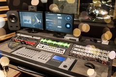 Music mixing console at sound recording studio. Music, technology, electronics and equipment concept - mixing console and computer monitors at sound recording Stock Image