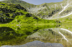 Music of the mountain. Symmetrical reflection resembling a musical instument, in the Fagaras Mountains, 2500m altitude, Romania Stock Photos