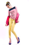 Music in my head. Pretty young girl isolated on white wearing bright casual clothes like yellow pants, stripped red white and blue shirt, pink vest,  purple high Stock Images