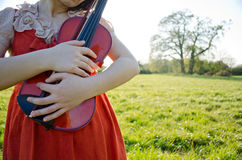 Music and nature in love. A young woman in nature, embracing a violin Royalty Free Stock Photo
