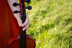 Music in nature. A womans hand holding a violin with a grassy background Royalty Free Stock Photo