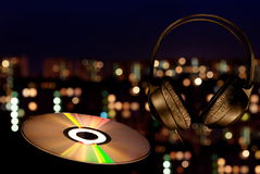 Music in a night city. Ear-phones and disk against a night city Stock Photos