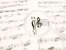 Music note sheet with a hand glass Stock Photos