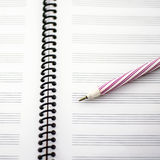Music notebook and red pen Royalty Free Stock Photos