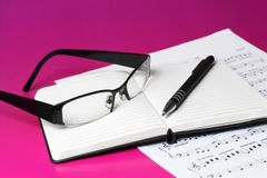 Music notes. Close up of reading glasses pen and open diary laid on printed piano sheet isolated on pink background Royalty Free Stock Image