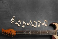 Music notes and guitar neck on grey background, top view. Space for text royalty free stock image