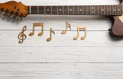 Music notes and guitar neck on wooden background. Top view. Space for text royalty free stock image