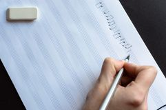 Music notes writing composer creating musician art. Side view of the hand writing the music notes with pencil. The concept of the music creating, composing, note royalty free stock image