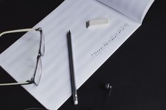 Music notes writing composer creating musician art. Top view of the pencil, eyeglasses and eraser laying on the sheet notes with handwritten notes. The concept royalty free stock images