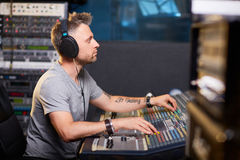 Music operator. Serious deejay or music operator working in recording studio Stock Photography