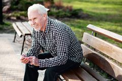 Dreaming senior man relaxing with music. Music outdoors. Vigorous senior man resting on bench and listening to music Royalty Free Stock Images
