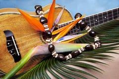 Music in Paradise. Still life of Hawaiian koa wood ukulele, with fresh bird of paradise flower and kukuinut lei, on blue backgound Stock Photography
