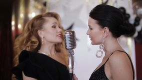 Two glamorous girls in evening gowns singing into a vintage microphone and having fun at the party stock video footage