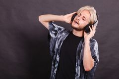 Blonde man singing in studio wearing headphones. Music, pasion, male artist concept. Blonde man singing in studio wearing big black headphones. Indoor shot on Royalty Free Stock Images