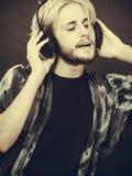 Blonde man singing in studio wearing headphones. Music, pasion, male artist concept. Blonde man singing in studio wearing big black headphones. Indoor shot on Royalty Free Stock Photography