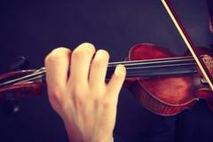 Man man dressed elegantly playing violin Stock Images