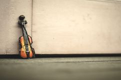 Music passion and hobby concept, violin miniature over wooden wall with retro color tone Royalty Free Stock Photo