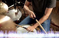Musician playing drums at sound recording studio. Music, people and entertainment concept - close up of male musician with drumsticks playing drum kit at concert Stock Images