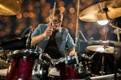 Musician playing drum kit at concert over lights. Music, people, musical instruments and entertainment concept - male musician or drummer with drumsticks playing Royalty Free Stock Images