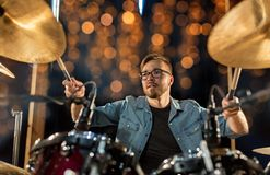 Musician playing drum kit at concert over lights. Music, people, musical instruments and entertainment concept - male musician or drummer with drumsticks playing Stock Images