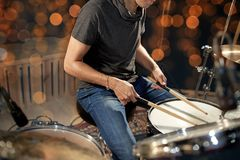 Musician or drummer playing drum kit at concert. Music, people, musical instruments and entertainment concept - male musician or drummer playing drum kit at Royalty Free Stock Photo