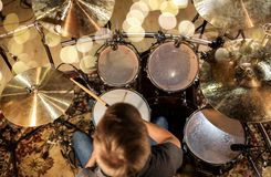 Musician or drummer playing drum kit at studio. Music, people, musical instruments and entertainment concept - male musician or drummer playing drum kit at Stock Photo