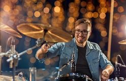 Musician or drummer playing drum kit at concert. Music, people, musical instruments and entertainment concept - male musician or drummer playing drums and Royalty Free Stock Images