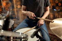 Musician playing drum kit at concert over lights. Music, people, musical instruments and entertainment concept - male musician or drummer playing drums and Royalty Free Stock Images