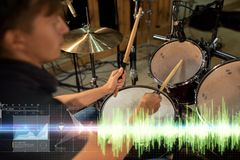 Male musician playing drum kit at concert. Music, people, musical instruments and entertainment concept - male musician with drumsticks playing drum kit at Stock Photography