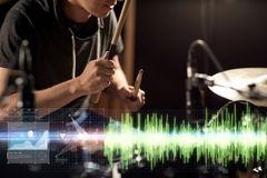 Male musician playing drum kit at concert. Music, people, musical instruments and entertainment concept - male musician with drumsticks playing drum kit at Royalty Free Stock Images