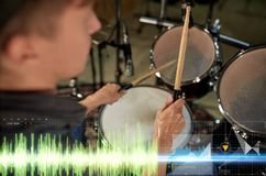 Male musician playing drum kit at concert. Music, people, musical instruments and entertainment concept - male musician with drumsticks playing drum kit at Royalty Free Stock Photography