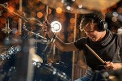 Male musician playing drum kit at concert. Music, people, musical instruments and entertainment concept - male musician in headphones with drumsticks playing Stock Images