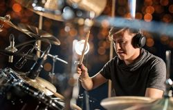 Male musician playing drum kit at concert. Music, people, musical instruments and entertainment concept - male musician in headphones with drumsticks playing Royalty Free Stock Images