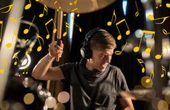 Musician in headphones playing drum kit at concert Royalty Free Stock Photo