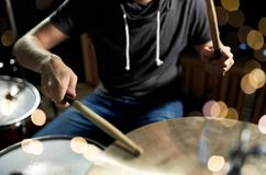 Male musician playing drum kit at concert. Music, people, musical instruments and entertainment concept - male musician playing drum kit at concert or studio Stock Image
