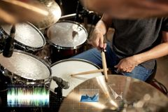 Male musician playing drum kit at concert. Music, people, musical instruments and technology concept - male musician playing drum kit at concert or studio Stock Image