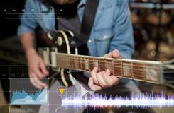 Close up of man playing guitar at studio rehearsal. Music, people and recording studio concept - close up of male guitarist playing electric guitar and sound Stock Photo