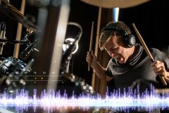 Musician playing drums at sound recording studio. Music, people and technology concept - male musician in headphones with drumsticks playing drums and cymbals at Royalty Free Stock Photography