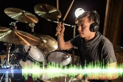 Musician playing drums at sound recording studio. Music, people and technology concept - male musician in headphones with drumsticks playing drums and cymbals at Stock Image