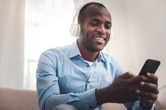 Delighted cheerful man looking at his smartphone royalty free stock images