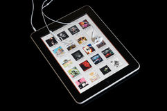 Music player on ipad with earphones Royalty Free Stock Photo