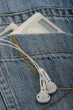 Music player and jeans. Music player with earphones and jeans stock photo