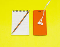 Music player, notebook with pencil on yellow background Royalty Free Stock Photography