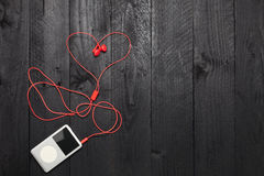 Music player with red earphone on black wood background. Stock Photos