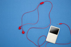 Music player with red earphone on blue paper background. Stock Images