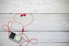 Music player with red earphone on white wood background. Stock Photos