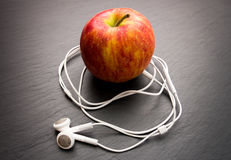 Music playing apple in which earphones are connected. royalty free stock images