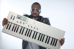 Music producer - being cool. Young black man with headphones and a keyboard. over white stock images